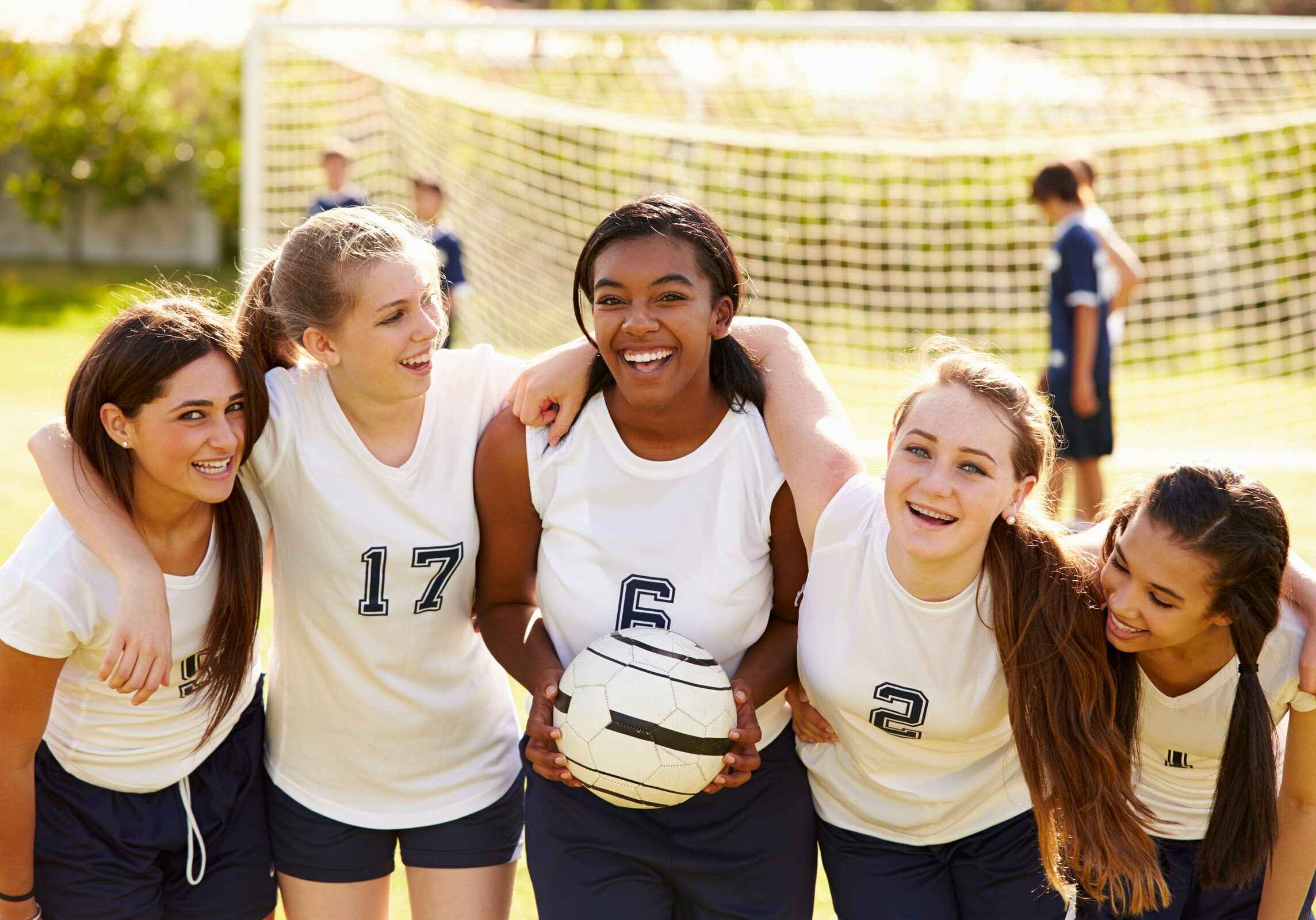 Members Of Female High School Soccer Team Smiling To Camera